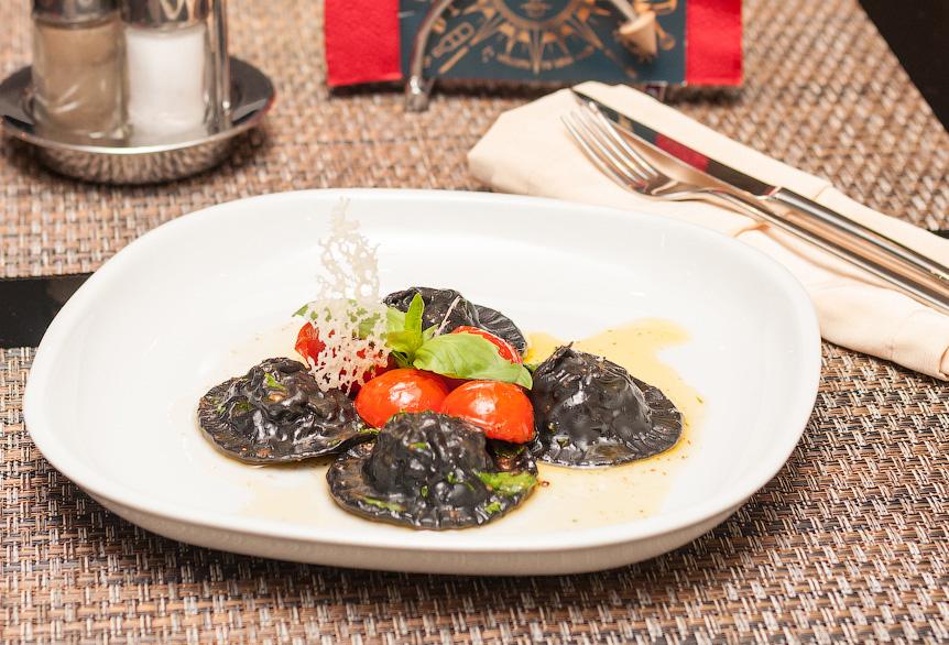 Черные равиоли  с лососем и рикоттой в соусе из базилика с томатами